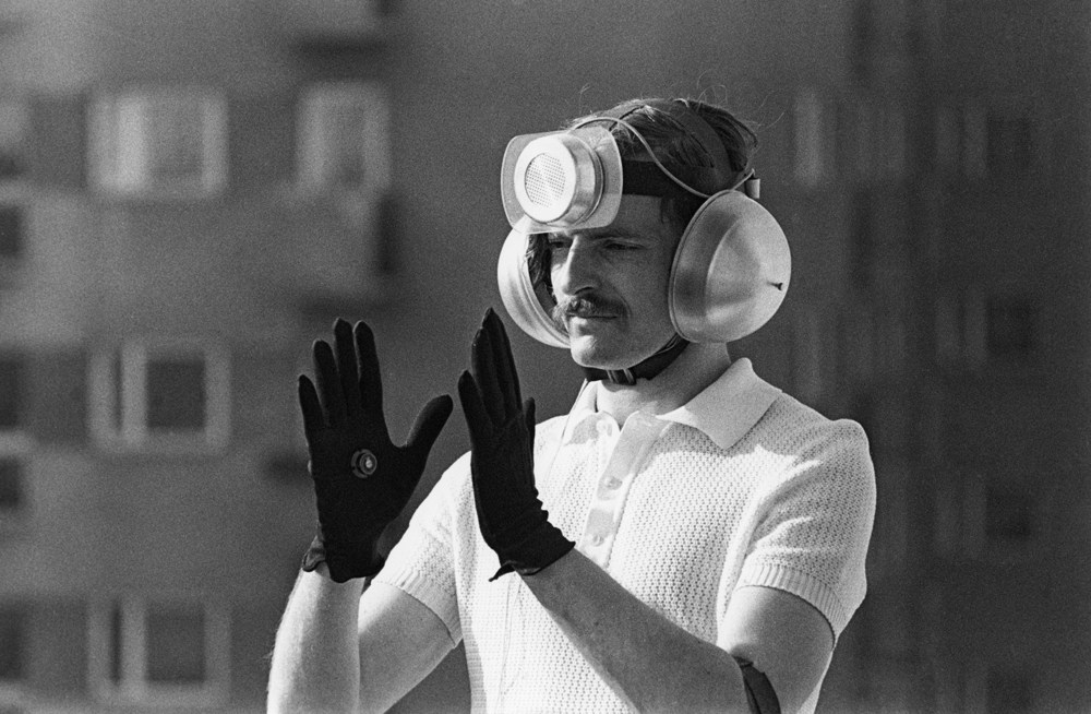 "Krzysztof Wodiczko, Personal Instrument, 1969-1972, photo courtesy of Łódź Art Museum "" The Personal Instrument consisted of a microphone, worn on the forehead, which retrieved sound while photo-receivers in gloves isolated and filtered the sound through the movement of the hand, which was then perceived discriminately by the artist, perceptually confined by the sound-proof headphones. By emphasizing selective listening, vital (under authoritarian restrictions) to a Polish citizen's survival, Wodiczko intimated the prevalence of censored speech, registering ""dissent of a system that fostered one-directional critical thinking – listening over speech."" (Kathleen MacQueen, Tactical Response, p.112, Agon Press, 2014) ""Personal Instrument"" can be regarded as an early expression of concern regarding Kemper's observation about ""a re-ordering of life (biological and social) under the cover of practices of media and communication""."